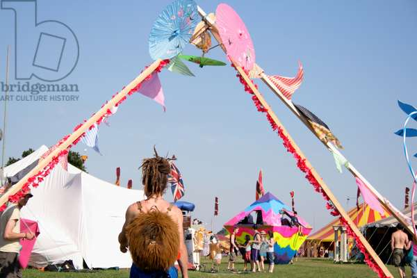 Girl with dreadlocks walking under some flags, Summer festival, at a music festival