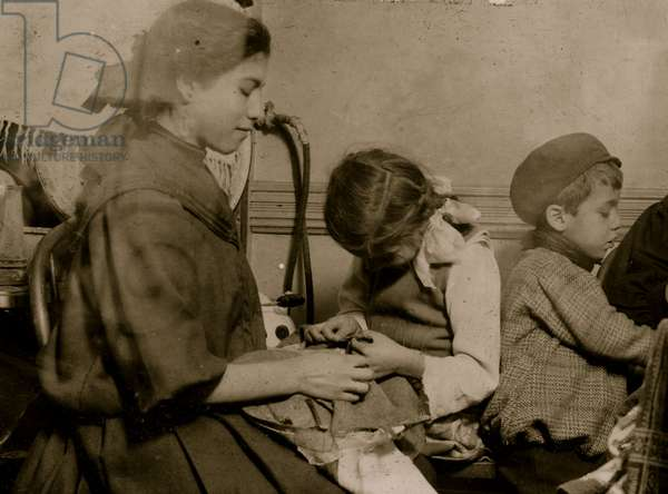 Italian Family works on garments in their tenement apartment 1911 (photo)