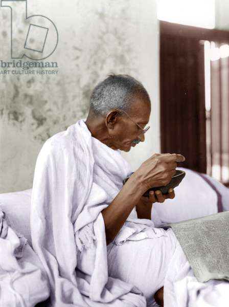 Mohandas Karamchand Gandhi dit Mahatma Gandhi (1869-1948), leader politique et spirituel indien mange une soupe a l'oignon en lisant le journal, Dandi (Inde), 7 avril 1930 - Mahatma Gandhi eating an onion soup while reading newspaper, Dandi, April 7, 1930. ©Dinodia/Uig/Leemage