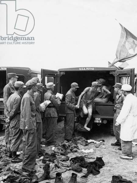 The North Korean repatriates shed every item of clothing issued by the Americans at the reception area. They came out only in short pants or nude and wore the Korean army caps which they had made in captivity, August 1953