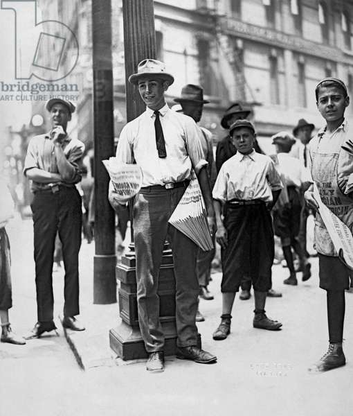 A young man selling newspapers on the street corner, Atlanta, Georgia, c.1920