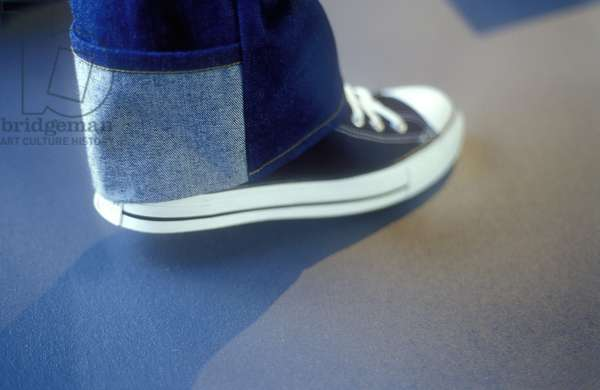 Close up detail of a Converse All Stars trainer and denim jeans at FIT (Fashion Institute of Technology) on display in New York USA 2002.