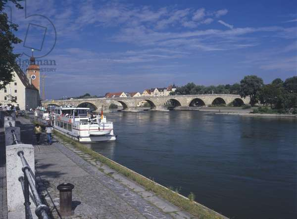 Germany, Bavaria, Regensburg, ratisbon, the picturesque Steiner Brucke, an outstanding example of medieval engineering spanning the Danube, leading to the old town of Regensburg. Passenger boats line the edge of the river.