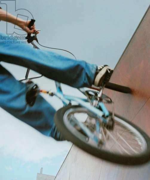 Wheels of a BMX bike on a ramp.