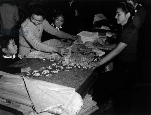 Mrs. Nakamura and family buying clothing, Manzanar Relocation Center, California, 1943 (photo)