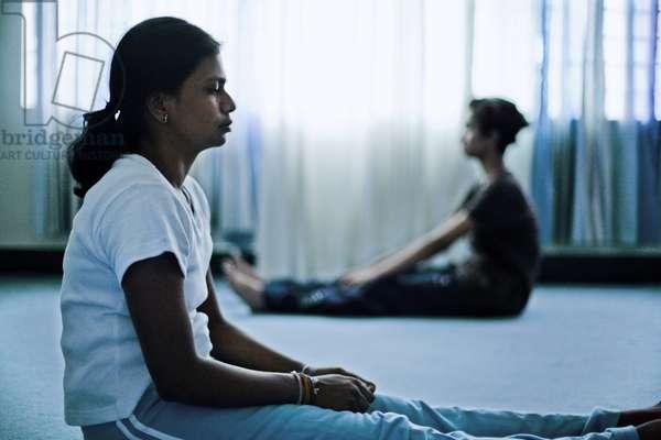 Mahilini Kailaiyangiri teaches her friends yoga in her dorm at the Asian University for Women. Chittagong, Bangladesh. July 2008.  (photo)
