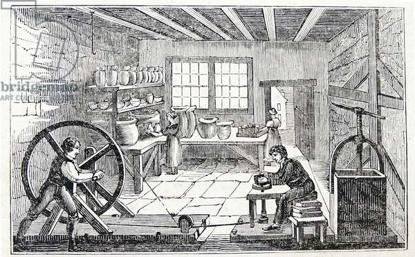 A potter's workshop: Boy turns wheel woks the belt which rotates the potter's wheel. Woodcut, London, 1936.