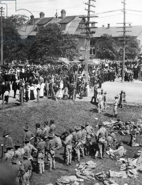 Calumet, Michigan: 1913 A parade of striking copper miners passing the offfices of the Calumet and Hecla Mining Company while National Guard troops stand by in case of trouble.  (b/w photo)