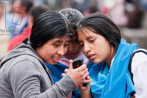 Young Women Watching A Mobile Phone on Plaza Grande, Quito, Pichincha, Ecuador (photo)