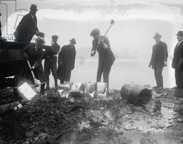 Police take axes & Picks to canisters of illegal alcohol during prohibition 1929 (photo)