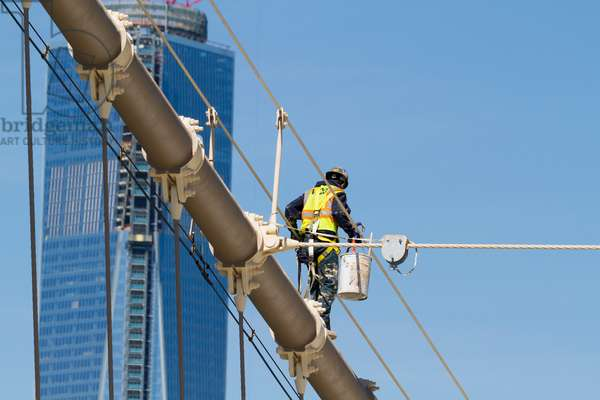 Man painting a suspension cable of the Brooklyn Bridge, New York City, New York, United States (photo)
