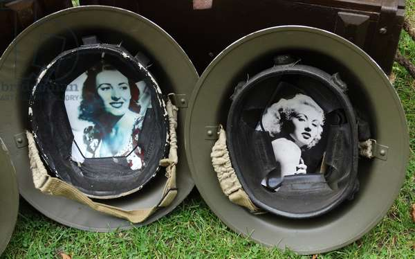Helmets of World War Two soliders with pictures of their wives lining the inside