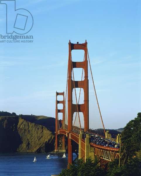 USA, California, San Francisco, Golden Gate Bridge, view towards craggy Marin headlands across traffic-laden bridge, sailing boats in blue waters underneath, blue sky background