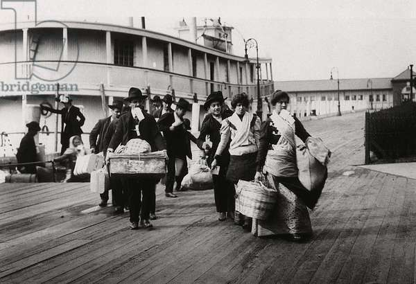 Imigrants to US landing at Ellis Island circa 1900. They head for the processing centre carrying paper with entry number which they hope will soon be traded for a visa.