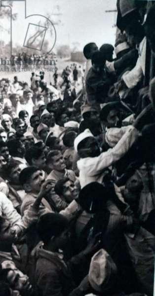 Crowds travel to New Delhi, to watch the cremation of Mohandas Karamchand Gandhi, India