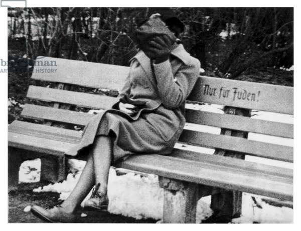 "A Jewish woman in Austria sitting on a bench marked ""Only for Jews"""