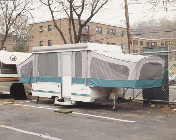 Parked caravan with canvas extensions, front view.