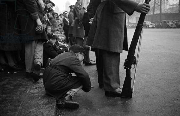 Child peers through legs to catch Princess Elizabeth's wedding, 1947