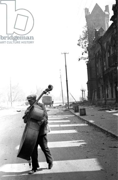 World War 2, Stalingrad, USSR, August 1942: a Contrabass Player on a Stalingrad Street.
