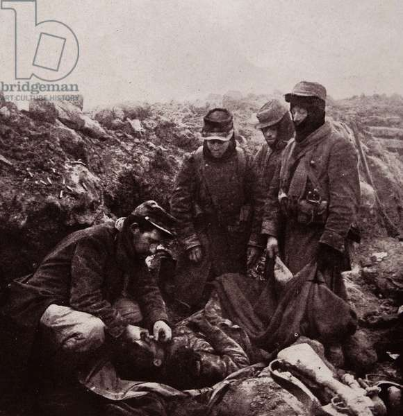 French Soldiers performing the last rites on a fallen comrade, 1915 (b/w photo)