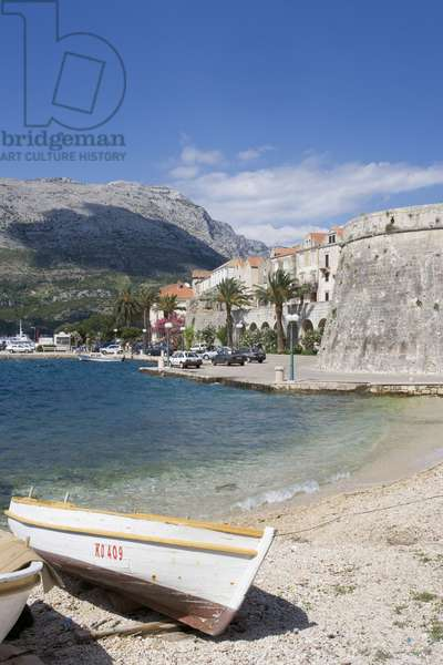 Croatia, Korcula, fortified walls overlooking waterfront and boast moored on beach on Dalmation coastline