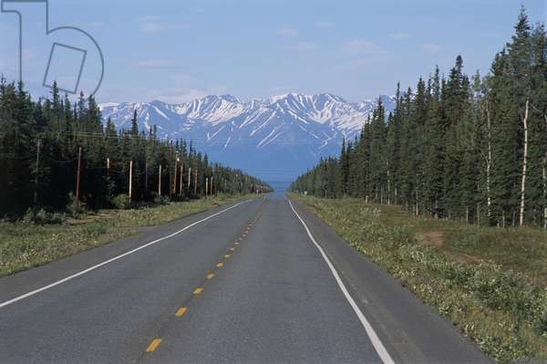 USA, Alaska, tree-lined straight Alaska Highway with snow-covered summit of Alaska Range mountain range in distance