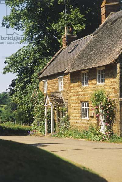 Great Britain, England, Oxfordshire, nr Banbury, thatched cottage on quiet country road, facade, side view.