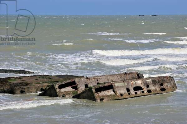 Concrete boxes, known as Phoenix caissons, in the sea were used as breakwater and to form an improvised harbour, Mulberry harbour, in front of Gold Beach during the Second World War at Arromanches, Normandy, France, 2010 (photo)