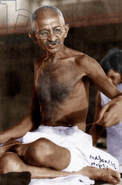 "Mohandas Karamchand Gandhi dit Mahatma Gandhi (1869-1948), leader politique et spirituel indien, filant lors de son voyage en Angleterre, sur le pont du Rajputana, 1931 - Mahatma Gandhi spinning on the sun deck during his voyage to England on board of S.S. Rajputana, September 10, 1931. Photograph is signed """"Mahatma Gandhi, 10-9-31"""". ©Dinodia/Uig/Leemage"