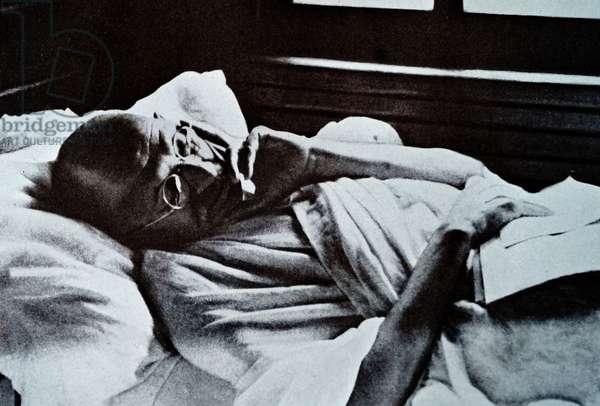 Mohandas Karamchand Gandhi resting during a rail journey to Delhi