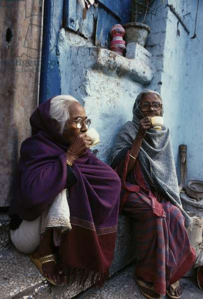 Sitting outside their house by a main road, old women drink tea. Calcutta, India.  (photo)