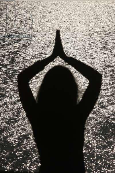 Woman praying at sunset (photo)