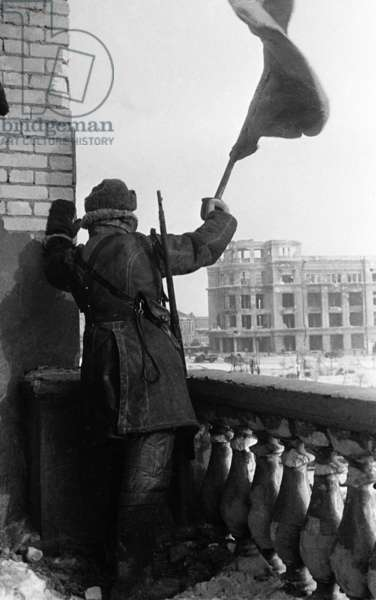 World War 2, Battle of Stalingrad, February 1943: a Red Army Soldier Raises the Soviet Flag (Hammer and Sickle) on the Roof of a Downtown Stalingrad Depatment Store