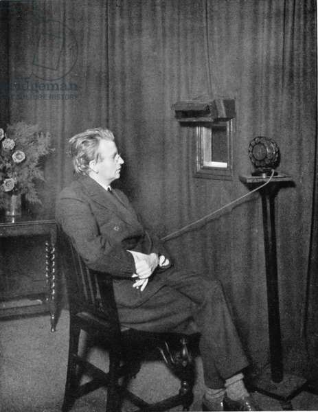 John Logie Baird (1888-1946) Scottish electrical engineer: pioneer of television. Baird giving early television ('Seeing by wireless') demonstration: image is of someone holding two dolls.