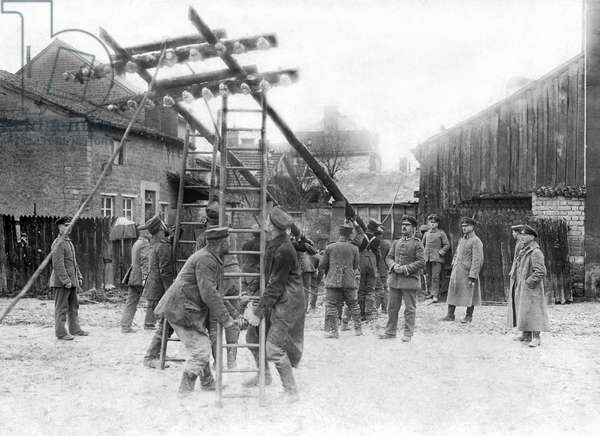 Champagne, France: c.1916 German troops erecting telegraph poles in a small village in Champagne.  (b/w photo)