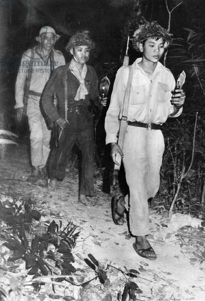 South Vietnamese Communist Guerrillas on the Ho Chi Minh Trail at Night, Vietnam War, 1964, Guerrillas Carrying Tiny Lamps Made from Perfume Bottles.