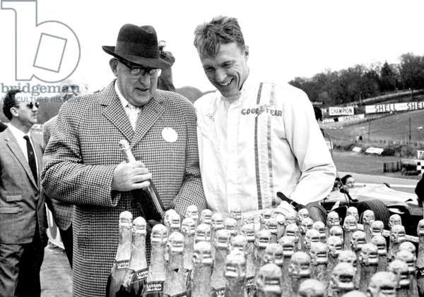 Dan gurney and eagle harry weslake looking at bottles of champagne, 1967 (photo)