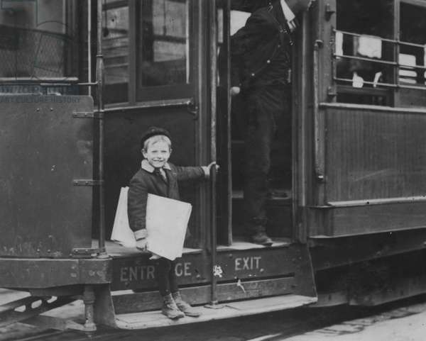 Francis Lance, 5 years old, 41 inches high. Sells regularly on Grand Avenue. He jumps on and off moving cars at risk of life. 1910 (photo)
