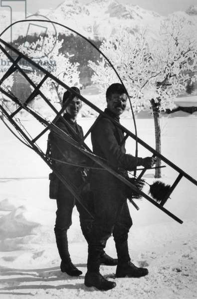 St. Moritz, Switzerland: c.1928 Two smiling chimney sweeps pause for a portrait with their tools of the trade.  (b/w photo)