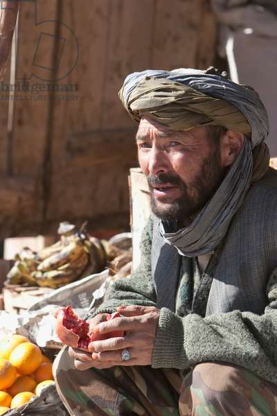 Afghan Man Enjoying A Pomegranate at the Bazaar in Bamiyan, Bamian Province, Afghanistan (photo)