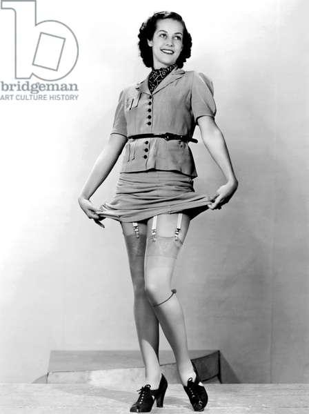 A Woman Displays Her Garters (b/w photo)
