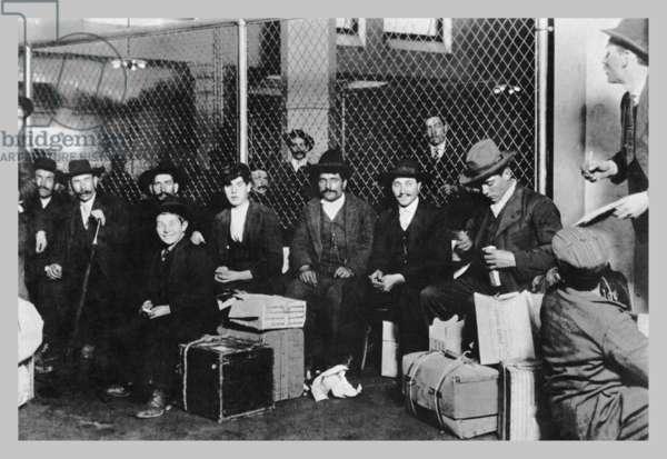 Immigrant Men Sitting at Ellis Island 1900 (photo)