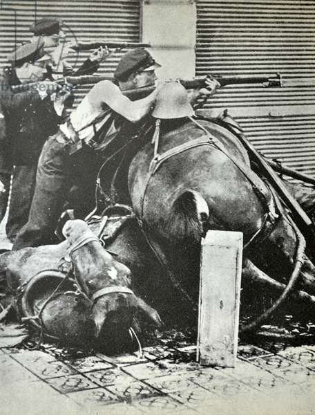 Three republican fighters take aim with rifles, behind a barricade made up of dead horses. Barcelona 1937, during the Spanish civil war 1938