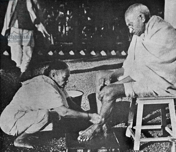Mahatma Gandhi having his feet washed, by his wife Kasturba.