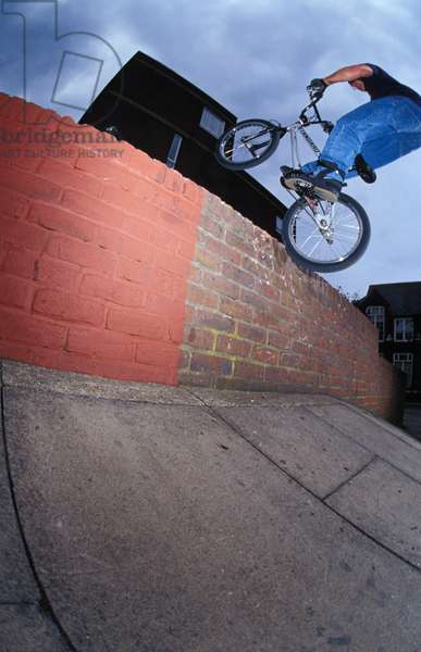 James Hitchcox on a BMX hopping on to a wall, UK, 2000's.