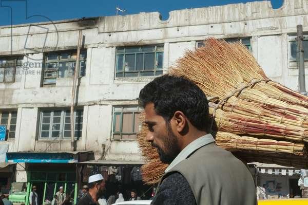 Afghan Man Carrying Brooms in Kabul, Afghanistan (photo)