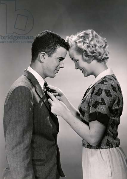 Woman with coy look untying mans tie (b/w photo)
