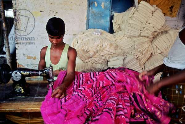 A young man works with sewing machine. Readymade Garments Industry (RMG), the most contributing economic sector of Bangladesh employs a good number of young people. Bangladesh.  (photo)