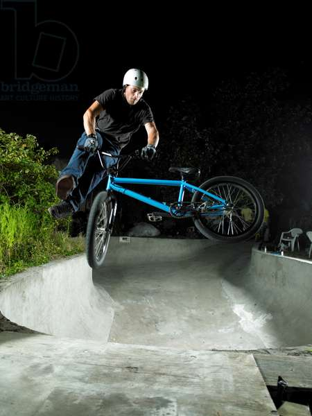 Man on a blue bmx doing tail-whip in a backyard pool at night, UK