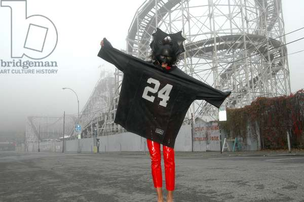 A girl in an oversized sports jersey and mask posing on a misty day in front of a fairground, USA 2004.